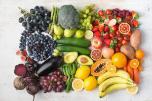 Healthy eating concept, assortment of rainbow fruits and vegetables, berries, bananas, oranges, grapes, broccoli, beetroot background