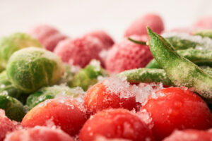 Closeup of frozen asparagus bean pods and cherry tomatoes with strawberries: frozen food concept.
