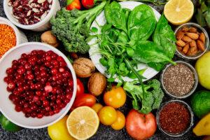 fruits, vegetables, cereals, nuts, oils, dark grey concrete background