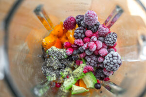 Macro shot of what's inside a blender: avocado, apricot, frozen berries, chia seeds.