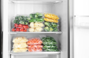 Plastic bags with different frozen vegetables in refrigerator