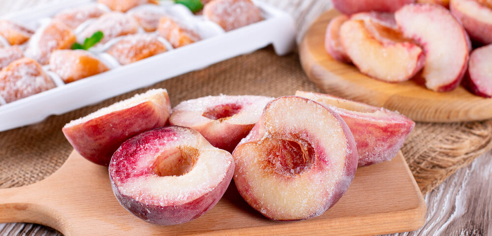 Organic frozen fruits (peaches, apricots) on a wooden board