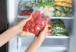 Woman holding plastic bag with frozen tomatoes near open refrigerator, closeup