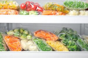Plastic bags with deep frozen vegetables in refrigerator - Sunleaf Foods