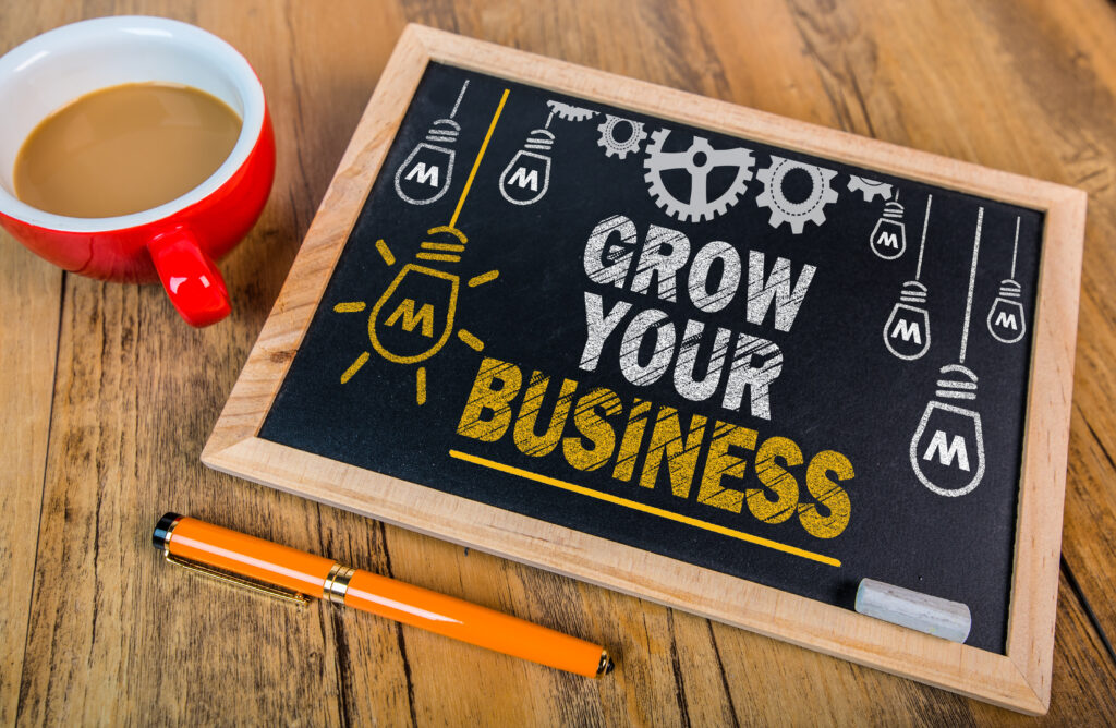 grow your business sign on table beside a cup of coffee and a pen